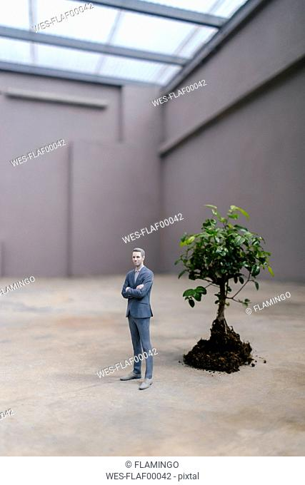 Businessman figurine standing next to a little tree