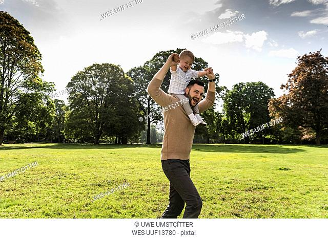 Happy father carrying son on shoulders in a park