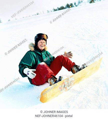 Woman with snowboard sitting on the ground, laughing