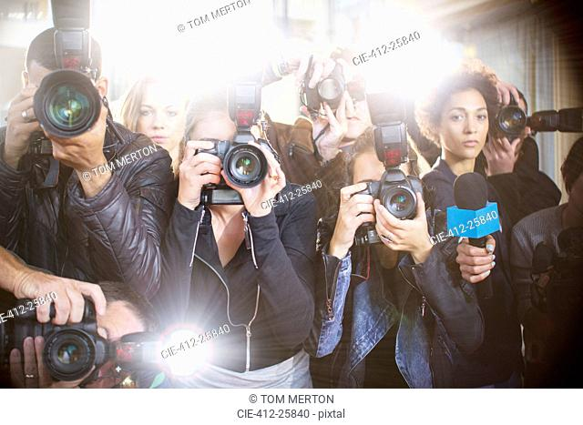 Portrait of serious paparazzi photographers pointing cameras