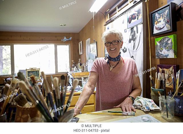 Portrait smiling senior woman artist painting in art studio
