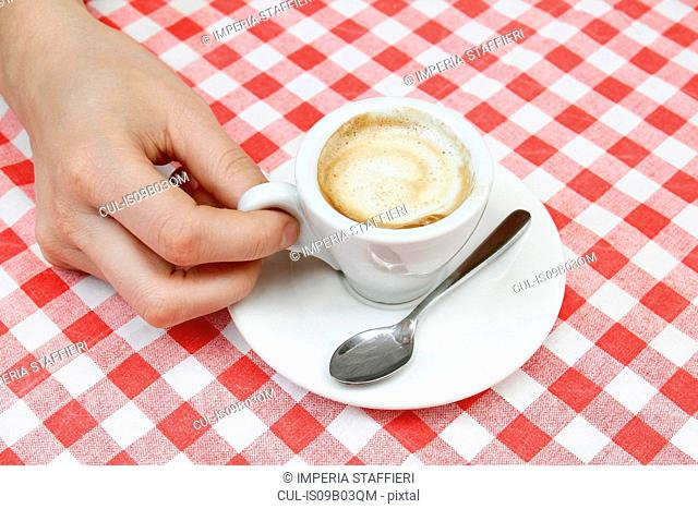 Woman's hand with espresso at sidewalk cafe table, Milan, Italy