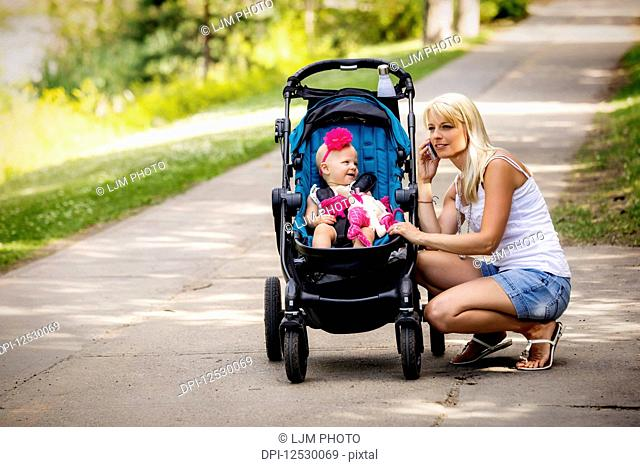 A beautiful young mother taking her baby daughter out for a walk using a stroller in a park with a lake on a warm sunny day and stopping to take a call on her...