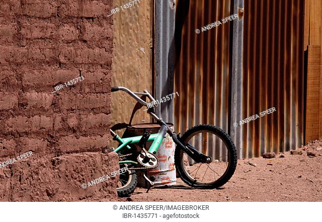 Old child's bike leaning against a loam wall, Chile, South America