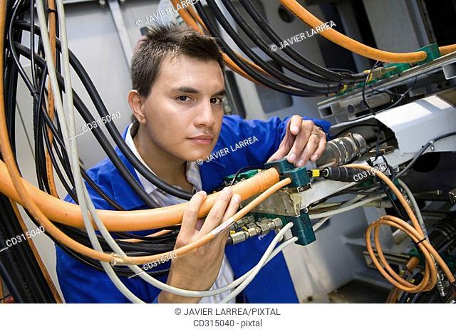 Fatronik Research Centre, San Sebastian Technological Park, Donostia, Gipuzkoa, Basque Country. Technician checking the electric and hydraulic systems of a...