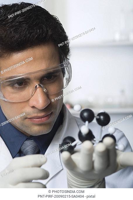 Scientist holding molecular model in a laboratory