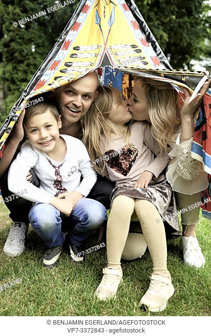 Happy family inside tipi in garden