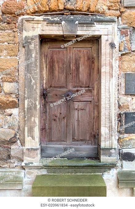 Alte braune verwitterte Holztür in einem steinernen Portal