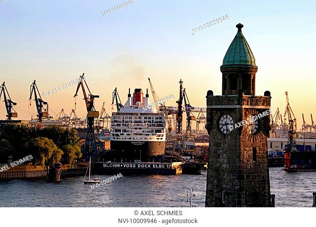 Silhouette of the Landungsbruecken with passenger cruise ship Queen Mary 2 in the shipyards, Hamburg, Germany