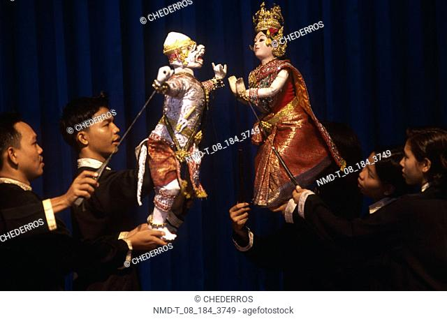 Close-up of four puppeteers performing with puppets, Thailand