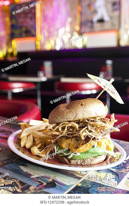 Vegan burger with avocado, soy cheese, fried onions and french fries