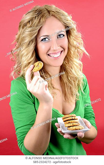 Blond young girl holding a plate of chocolate chip cookies