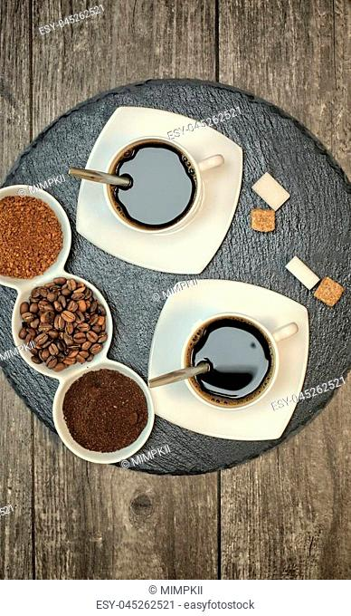 Two cups of coffee on a dark slate stand and wooden background