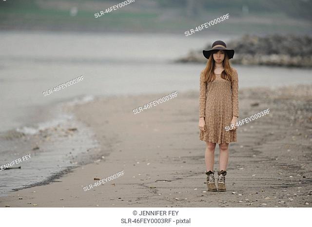 Teenage girl standing on sandy beach