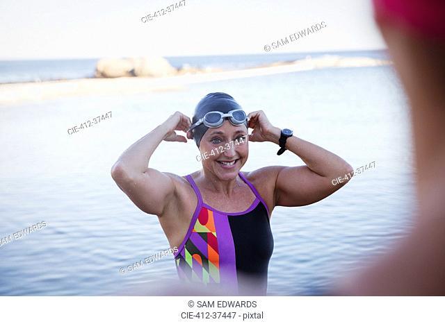 Smiling female open water swimmer adjusting swimming cap and goggles in ocean