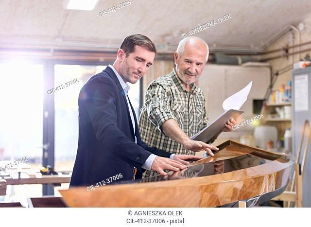 Male carpenter and customer examining wood kayak in workshop
