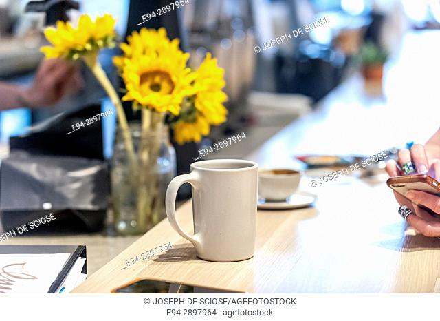 Partial view of fingers on a mobile phone in a coffee shop with a bouquet of sunflowers and a coffee cup