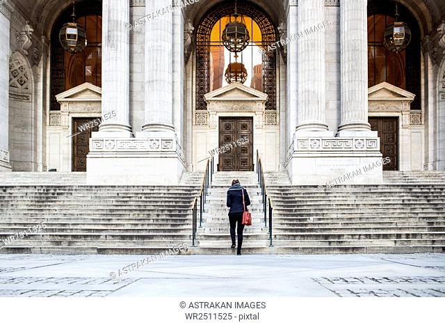 Rear view of businesswoman walking towards New York Public Library