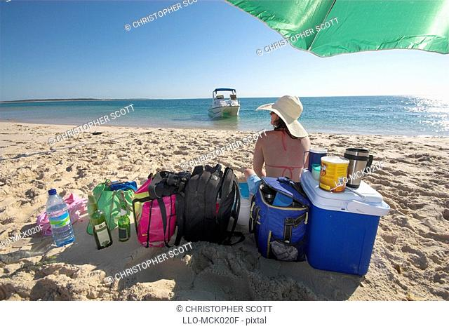 Woman Sitting on the with Cooler Bags and Luggage  Bazaruto Archipelago, Mozambique