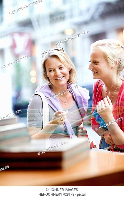 Mother and daughter looking at shop window