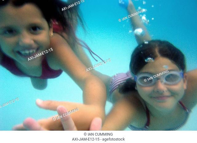 Young girls under water in swimming pool, Jamaica