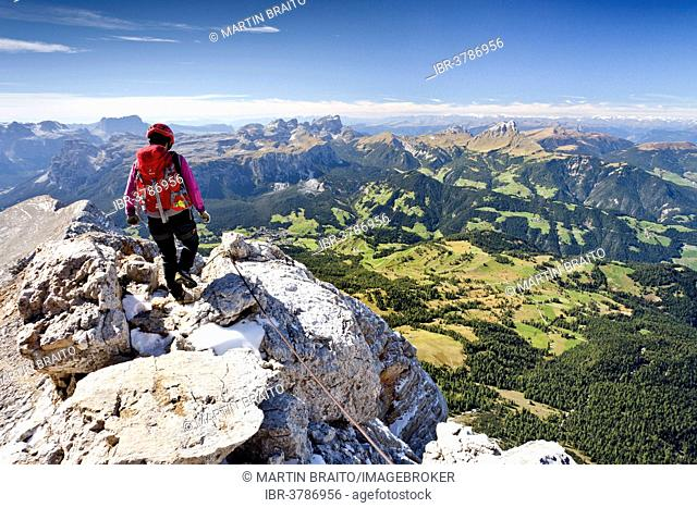 Climber descending from the Zehnerspitze over the Zehner-Ferrata in the Fanes, Fanes-Senes-Prague, view of the Val Badia, the Puez and the Sella, Dolomites