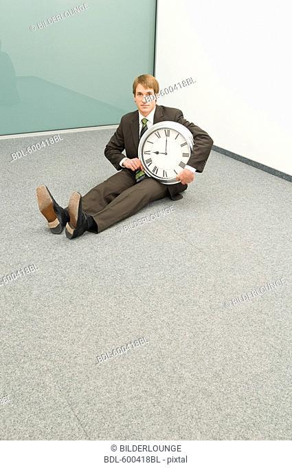 businessman sitting in corner holding clock