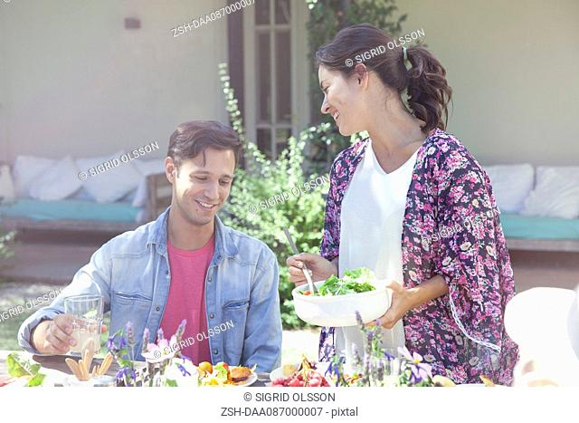 Wife serving salad to husband