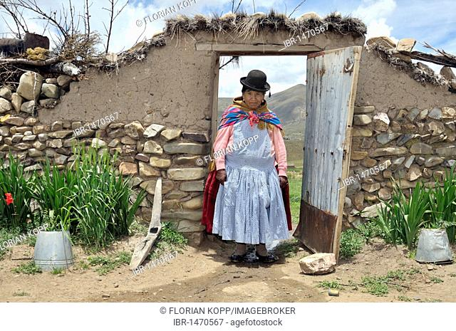Portrait of a woman in traditional dress of the Quechua in a yard gate, Bolivian Altiplano highlands, Departamento Oruro, Bolivia, South America