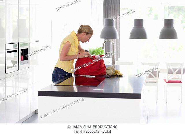 Woman unpacking groceries from shopping bag