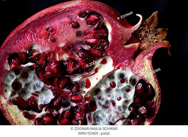 Sliced Pomegranate with arils on black glass
