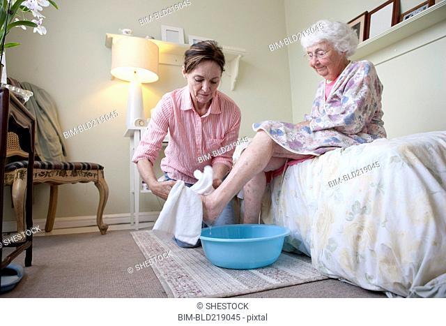 Caregiver washing foot of older woman in bedroom