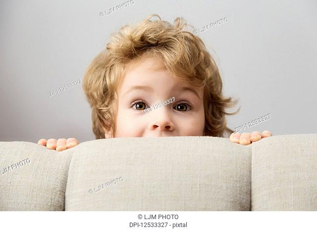 Portrait of a young boy peeking out from behind a couch and looking at the camera; Langley, British Columbia, Canada