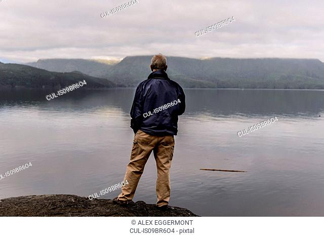 Man relaxing by lakeside, Johnstone Strait, Telegraph Cove, Canada