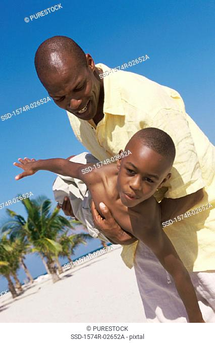 Father carrying his son on the beach