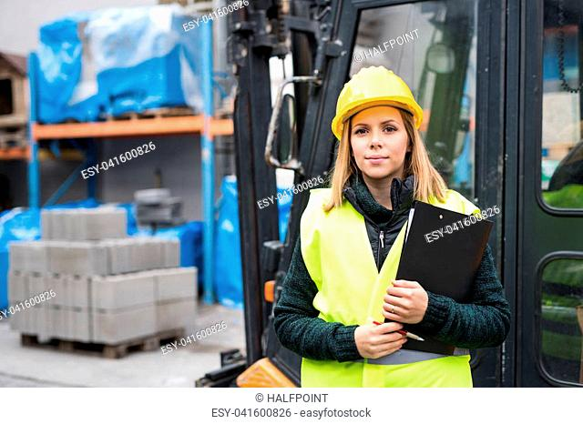 Woman forklift truck driver in an industrial area. A woman standing in front of the fork lift truck outside a warehouse