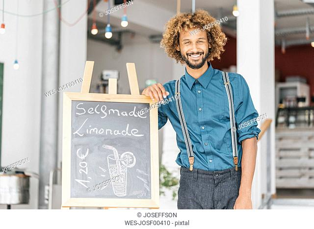 Young man standing in his own coffee shop
