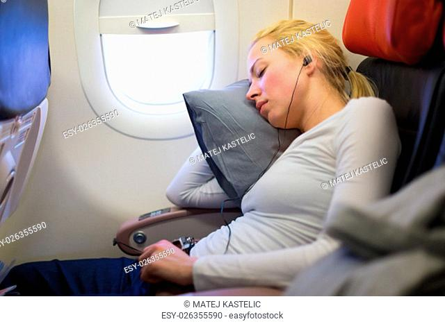 Tired blonde casual caucasian lady listens to music while napping on uncomfortable seat while traveling by airplane. Commercial transportation by planes