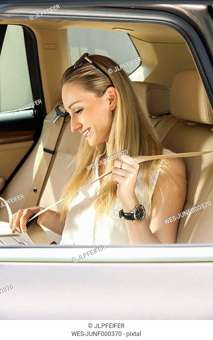 Blond woman putting on safety belt at back seat of a car