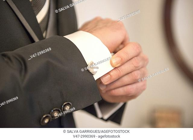 The groom adjusts the sleeve of the suit revealing the twin of the shirt