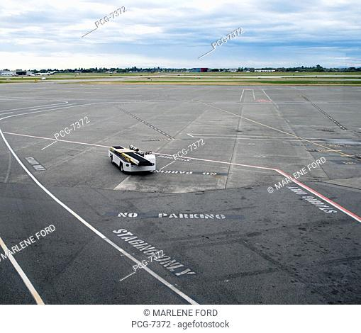 View from above. The airport apron, tarmac, marked out areas, for service vehicles. Airside. A luggage conveyor truck, low loader, vehicle