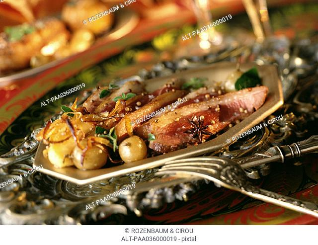 Sliced duck with caramelized onions on plate, close-up