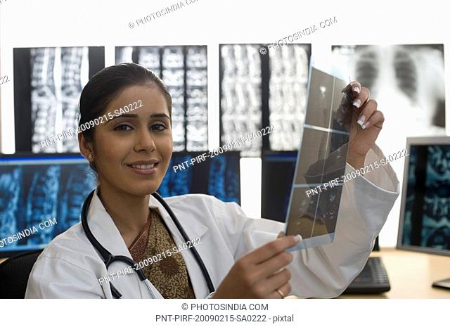 Portrait of a female doctor holding an X-Ray report and smiling