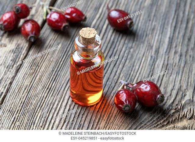 A bottle of rose hip seed oil with dried berries