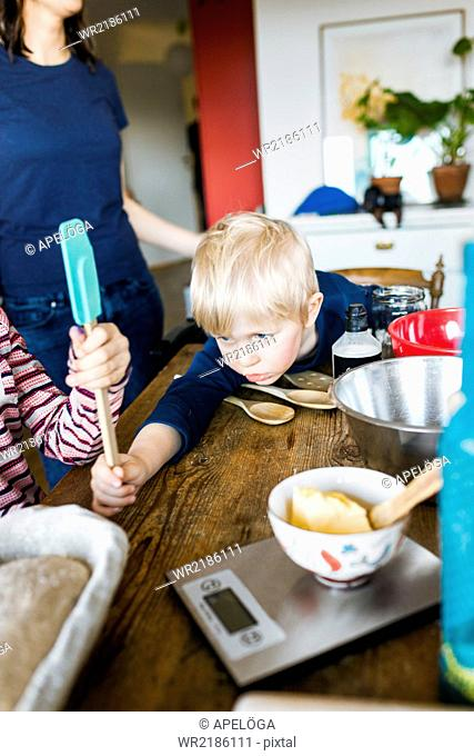Little boy with sister holding scraper while mother standing at table