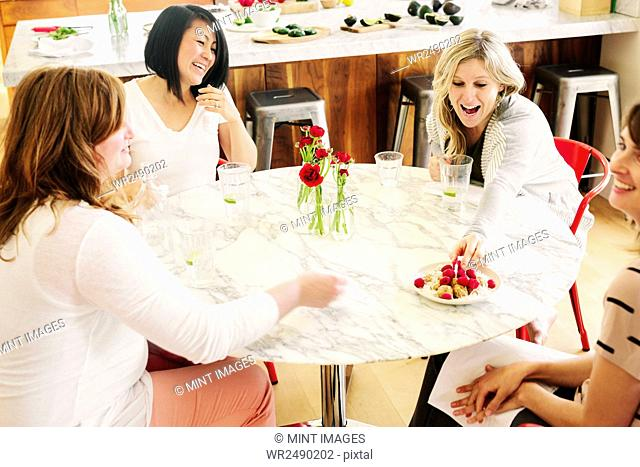 Four friends around a table having lunch together