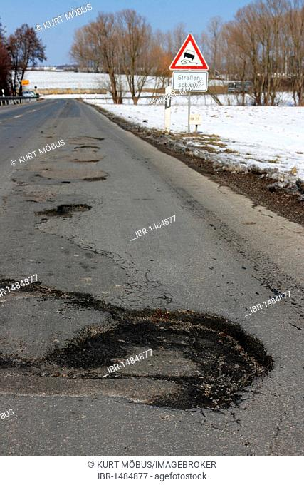 Warning sign, road damage, potholes in an asphalt road caused by frost damage in the cold winter 2009-2010