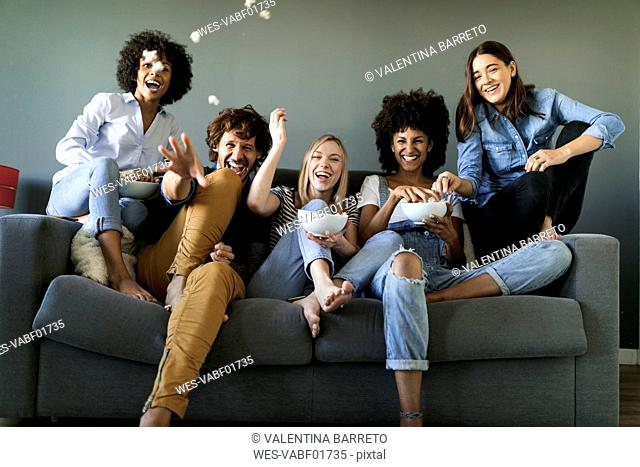 Exuberant friends sitting on couch throwing popcorn
