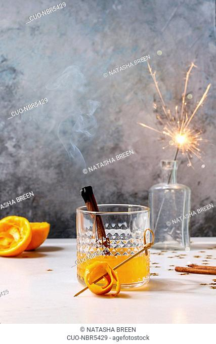 Glass of Scotch Whiskey orange juice alcohol cocktail with swirled orange peel and smoking cinnamon sticks standing on white marble table with golden holiday...