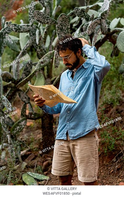 Young man standing in nature, looking at map